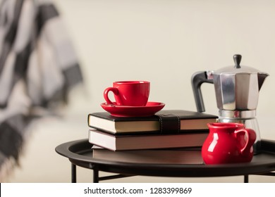 Round black metal coffee table with a coffee maker and a cup with books on the background of a white sofa with a gray plaid. Selective focus