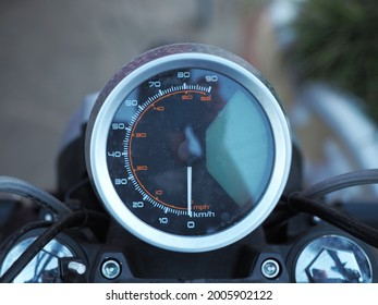 Round black spattered motorcycle speedometer. Front view. Closeup photo with blurred background