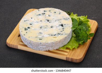 Round blue cheese with salad and basil