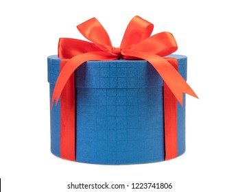 Round blue gift box with red bow on a white background.