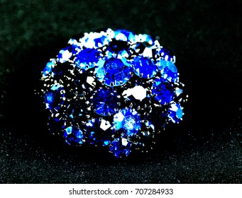 Round blue jeweled pin on a black background