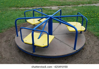 Round blue swing for children with yellow seats in a public park.