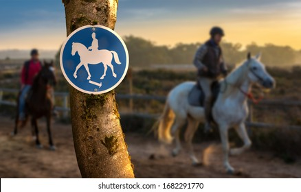 A round blue and white sign marks a bridle path in Spain. Here it is allowed to ride horses. In the background out of focus with bokeh two horsemen and a landscape at sunset.