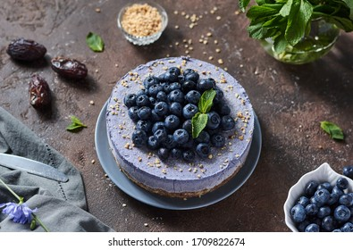 round blueberry vegan cheesecake with berries on a brown background top view