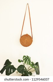Round boho rattan bag with a leather strap isolated on white wall with a monstera plant standing underneath