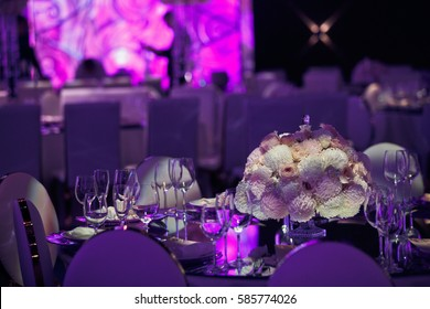 Round bouquet of roses and chrysanthemums stands in the middle of dinner table in dark hall