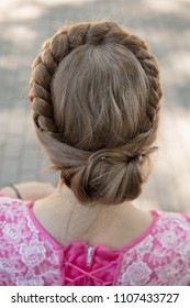 Round braid of hair on the head of a girl