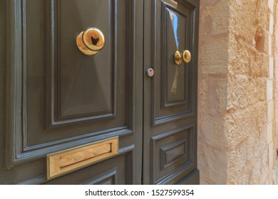 Round brass knob, keyhole, hole for letters, on luxurious doors in Mdina, Malta
