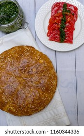 Round bread with sesame, pesto, tomatoes and salt with spices