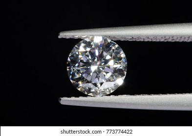 Round brilliant cut diamond on on tweezers with black background