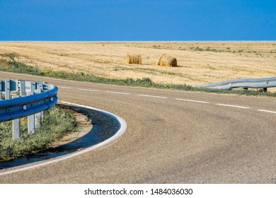 Round briquettes with straw after harvesting wheat on a field near an asphalt road