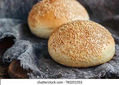 Round bun, sesame bun, bread rolls. Tasty burger bread with sesame on wooden, burlap background. Freshly baked hamburger buns. Top view.