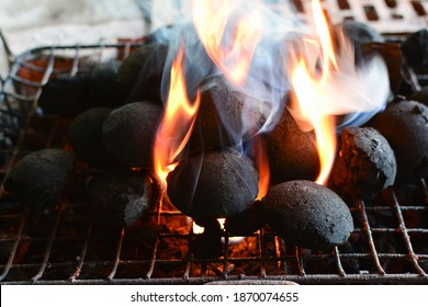 Round charcoal briquettes for barbecue on gril, fire started, flames and smoke break through between the coal briquettes, horizontal orientation