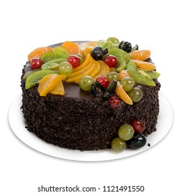 Round chocolate cake with crumbs covered in fresh fruits, with grapes, tangerine slices and kiwi, on a white plate isolated on white background