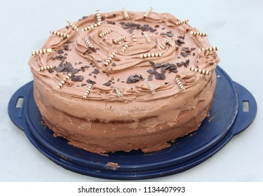 A round chocolate cake with embellishments and an inscription