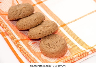 Round chocolate cookies on the kitchen table cloth.