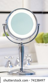 Round chrome lighted makeup mirror in bathroom. Green towels in the background.