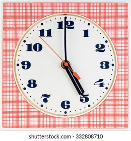 Round clock face on red striped background showing five o'clock