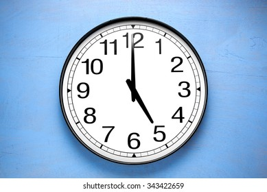 Round clock shows shows at 5 o'clock, clock on blue  background