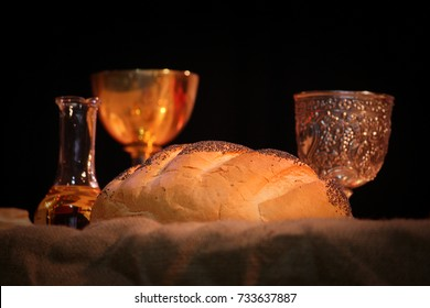 round cobb bread loaf, wine in a brass goblet glass and water on a table cloth with soft golden light ready for easter liturgy or church religious ceremony