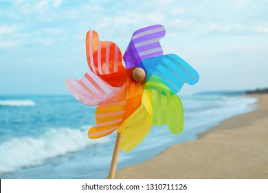 A round colored pinwheel with blowing wind stands in the sand by the sea against the backdrop of strong waves. Plastic windmill, toy on the sea beach