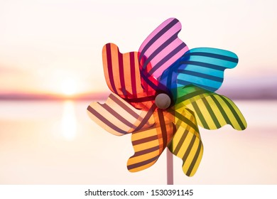 A round colored plastic pinwheel with a blowing wind stands on the sand by the sea against the smooth surface of the sea and a bright pink sunset. Toy mill on the sea beach. Large disk sun. Copyspace