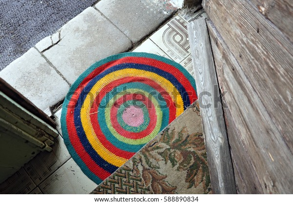 Round colored striped rug doormat at the entrance of the old building. Look down.