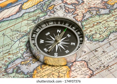 Round compass and ancient map (close up).