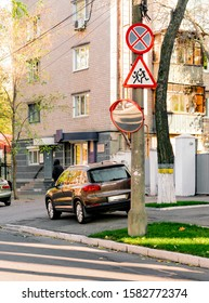 Round convex mirror installed on concrete pole. Crossing streets. Safety. No parking no stopping sign. Children run road sign. Street. Urban. City
