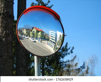 Round convex traffic mirror on the alley for better visibility. Convex mirrors provide a wider field of view on roads, driveways and in alleys.