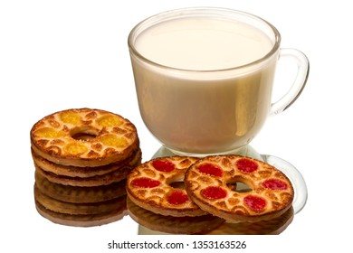 Round cookies and a transparent cup of milk on a mirror isolated on white background