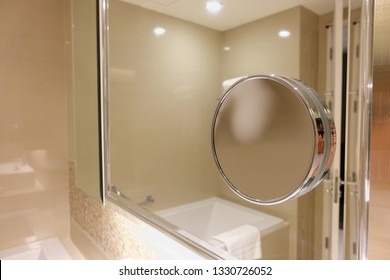 Round cosmetic mirror on the Square mirror hanging on a white wall in the luxury bathroom.