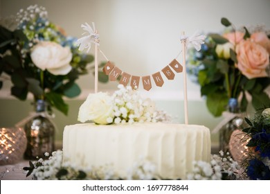 Round cream wedding cake and flower arrangement with cream and peach roses, dark green leaves,forget-me-not flower and baby wreath, candles in the glasses