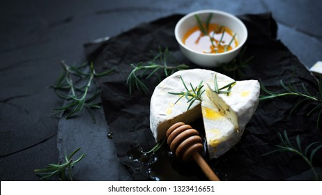 Round creamy soft camembert cheese with rosemary and honey on dark slate.Traditional Camembert or Brie cheese. Eye bird view.