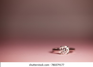 Round cut solitaire engagement ring romantic pink background