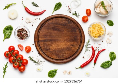 Round cutting board with pizza ingridients on white background, top view