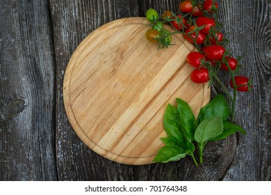 round cutting board and tomatoes on wooden surface