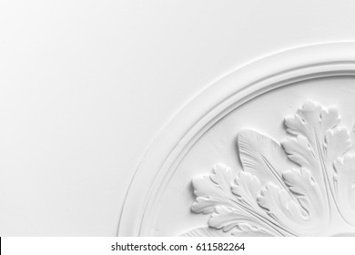 Round decorative clay stucco relief molding with floral ornaments on white ceiling in abstract classical style interior