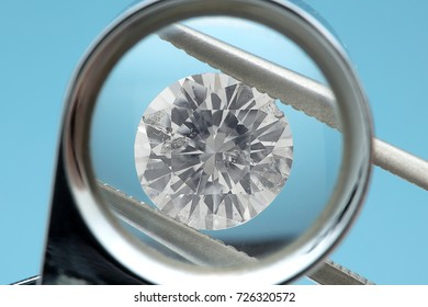Round diamonds is being looked through a 10x loupe top on blue background. It shows many flaws easily visible through the loupe close up