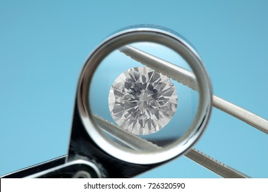 Round diamonds is being looked through a 10x loupe top on blue background. It shows many flaws easily visible through the loupe