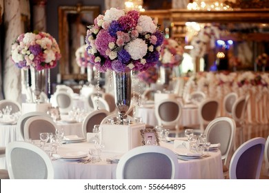 Round dinner table decorated with pink and violet hydrangeas stands in luxurious restaurant