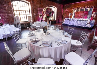 Round dinner table decorated violet flowers