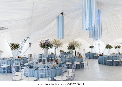 Round dinner tables covered with blue cloth stand in a white wedding pavilion