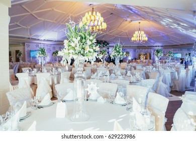 Round dinner tables covered with white clothes stand in bright restaurant hall