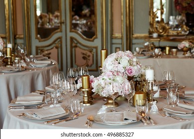 Round dinner tables decorated with golden candleholders and vases stand in rich Italian hall