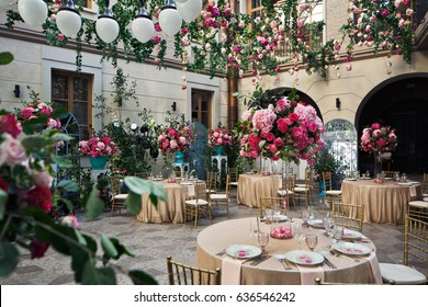 Round dinner tables with pink flowers stand on beautiful decorated backyard