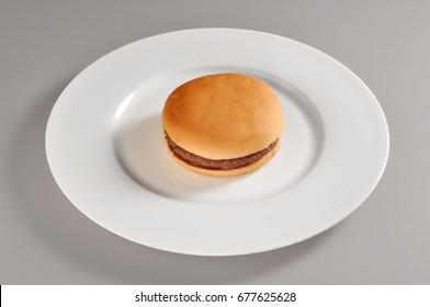 Round dish with a simple sandwich cheeseburgher isolated on grey background