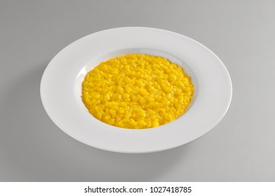 Round dish with yellow Milanese risotto  isolated on grey background