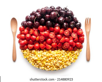 Round flag of Germany made of  tomato, cherry and corn kernels on a plate with wooden spoon and fork isolated on white