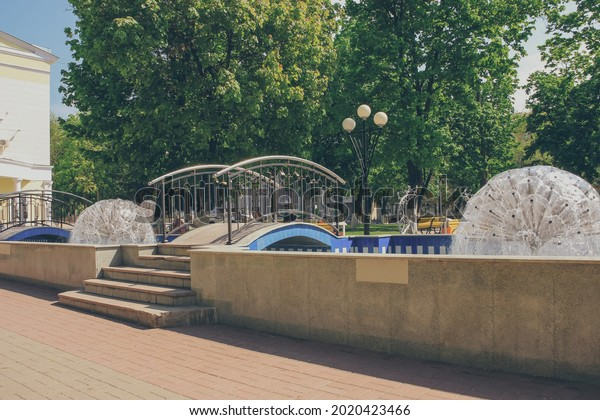 Round fountains with bridge and steps among green trees in city park